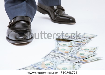 Feet of man in black shoes standing near the money track - closeup shot - stock photo