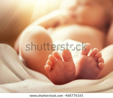 feet of newborn baby with soft blur effect, motherhood theme conceptual photo