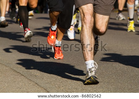 feet of some runners in a marathon competition - stock photo