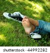 feet of the girl teenager and gym shoes on a green grass of a lawn in park - stock photo