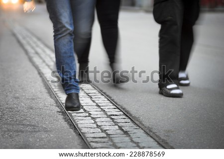Feet of three young men walking on street. Blurred motion.