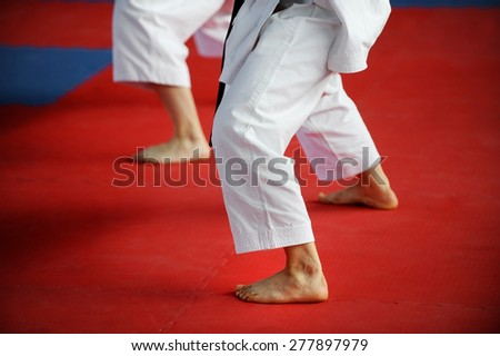 Feet of two karate practitioners are seen on the competition floor - stock photo