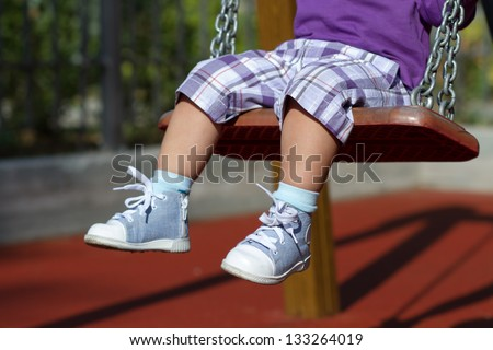 Feet of unrecognizable baby swinging on the playground alone - stock photo