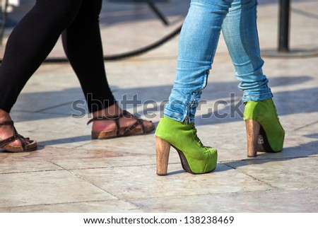 feet of walking women with sandals and pumps