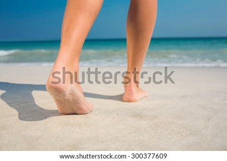 Feet of woman at the beach on a sunny day - stock photo