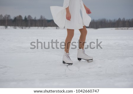 Feet of woman in white dress and skates on snow outdoors at winter