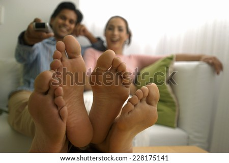Feet of young couple sitting on sofa - stock photo