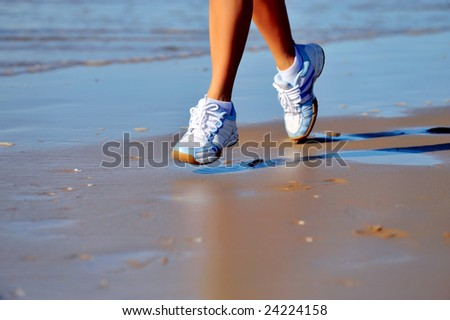 feet of young woman jogging on the beach - stock photo