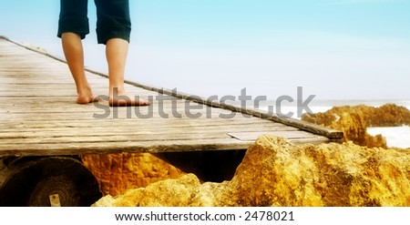 Feet of young woman standing on old bridge over a gorge at Knysna bay