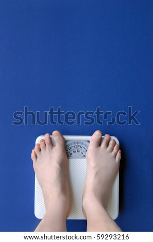 Feet on a scale with blue background - stock photo