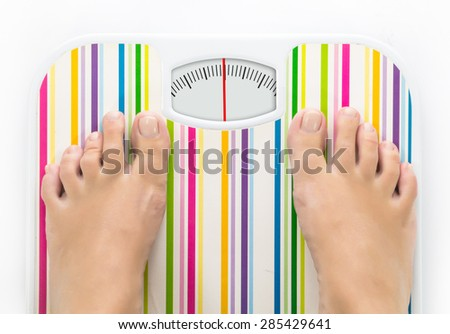 Feet on bathroom scale with clean dial with lines no numbers - stock photo