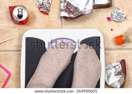 Feet on bathroom scale with junk food garbage around - stock photo