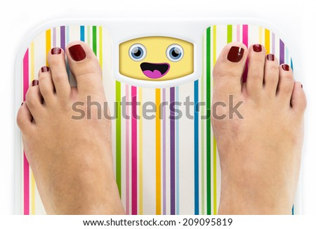 Feet on bathroom scale with laughing cute face on dial - stock photo