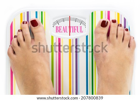 """Feet on bathroom scale with word """"Beautiful"""" on dial - stock photo"""