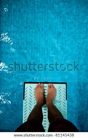 feet on diving board over pool - stock photo
