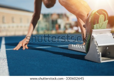 Feet on starting block ready for a spring start.  Focus on leg of a athlete about to start a race in stadium with sun flare. - stock photo