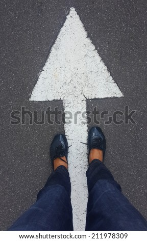 feet on tarmac road with white direction arrow - stock photo