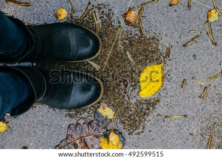 feet on the wet pavement and autumn leaves