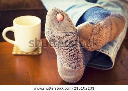 Feet propped up on a coffee table  with a pair of worn out socks with a hole and a toe sticking out of them. - stock photo