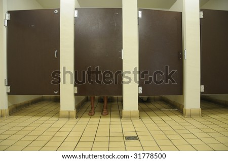 Feet showing under bathroom stall door, in public restroom with four stalls - stock photo