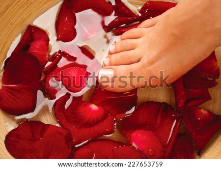 Feet Spa. Pedicure Concept. Beautiful healthy woman's feet massage. Female legs in water with rose petals - stock photo