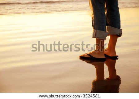 Feet standing at the ocean's edge at sunset - stock photo