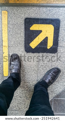 feet standing behind of the edge of a yellow line and yellow arrow on the stone floor