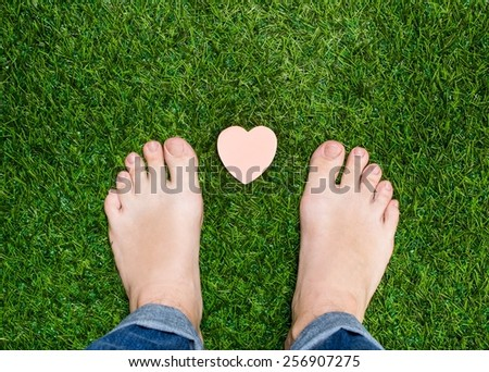 Feet standing on grass with small heart - stock photo