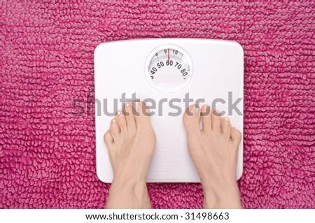 Feet tiptoeing on scales, shot landscape. - stock photo