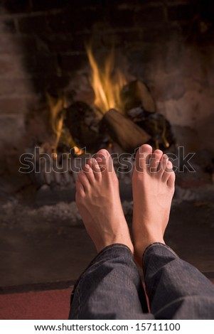 Feet warming at a fireplace - stock photo