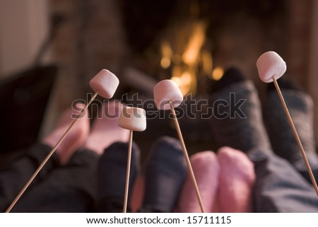 Feet warming at a fireplace with marshmallows on sticks - stock photo
