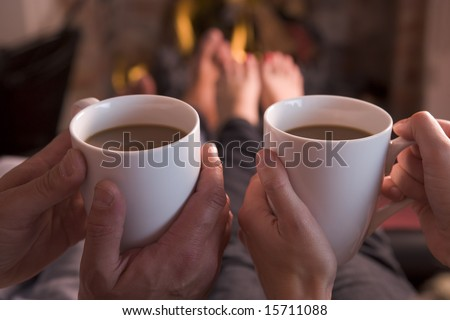 Feet warming at fireplace with hands holding coffee - stock photo