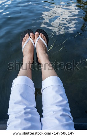 Feet Wearing White Flip Flop Hanging Over a Lake - stock photo