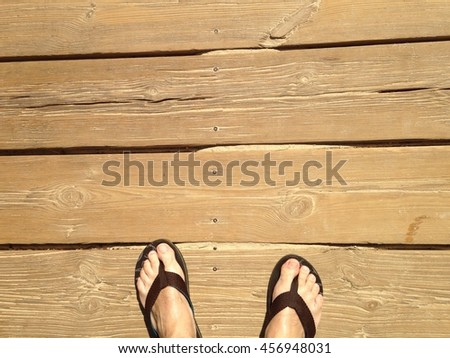 feet with flip flops on a wooden walkway on the beach - stock photo