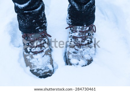 Feet with hiking boots in snow, concept of winter hiking - stock photo