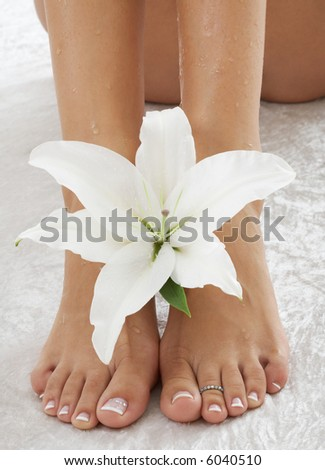 feet with madonna lily in spa (focus on flower) - stock photo
