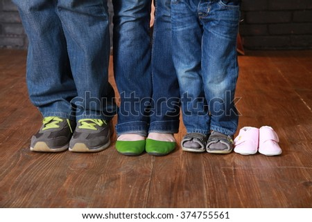 Feet with shoes of family members expecting a baby. Future parents feet and a pair of little shoes. Birth expectation concept - stock photo