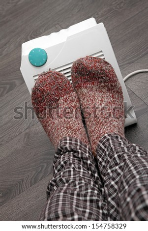 feet with wool socks and electric heater - stock photo