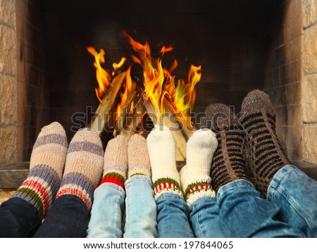 Feets of a family wearing woolen socks warming near the fireplace - stock photo