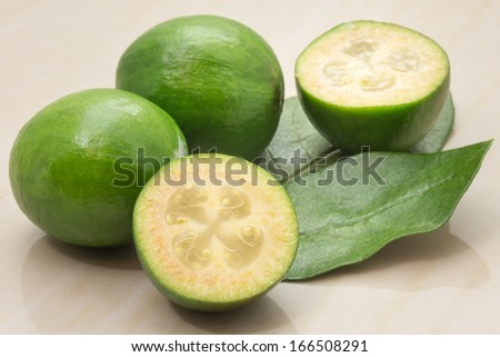 Feijoa fruit and leaves on a marble table