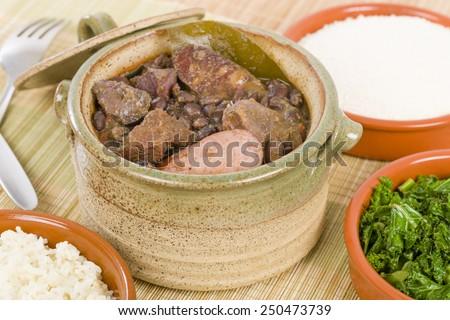 Feijoada - Brazilian beef, sausage, pork and black bean stew served with manioc flour, kale and white rice.  - stock photo