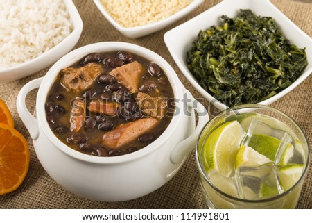 Feijoada - Brazilian beef, sausage, pork and black bean stew served with manioc flour, kale, white rice and oranges. Caipirinha drink on the side! - stock photo