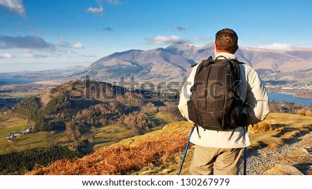 Fell walking on catbells mountain in the Lake District with a scenic panorama view of Derwentwater lake and Keswick in the background - stock photo