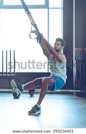 Fell your balance and strength. Full-length of young man in sportswear exercising at gym - stock photo