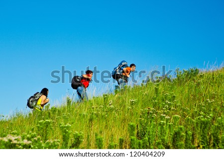 Fellow high school students with backpacks moving up the hill - stock photo