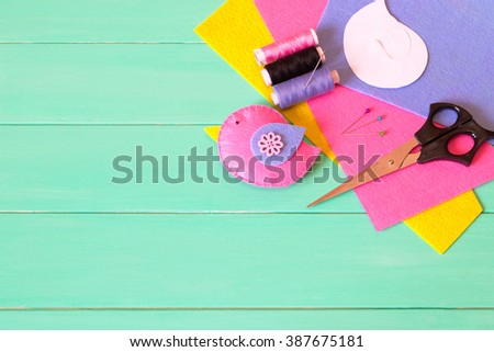 Felt bird, threads and a needle, sheets of felt, pins, scissors, paper templates - sewing set on a green wooden background with copy space - stock photo