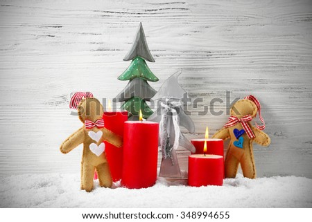 Felt dolls, red candles and fir trees in a snow over wooden background, still life