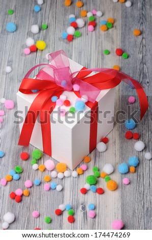 Felt pom poms and a white gift box - stock photo