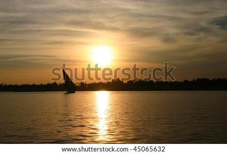 Felucca sailing on the River Nile against sunset. - stock photo