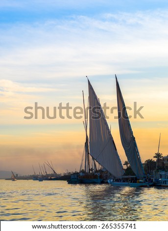 Felucca - traditional sail vessel on Nile river in Egypt. Romantic trip on egyptian boat at sunset. River cruise on the Nile.
